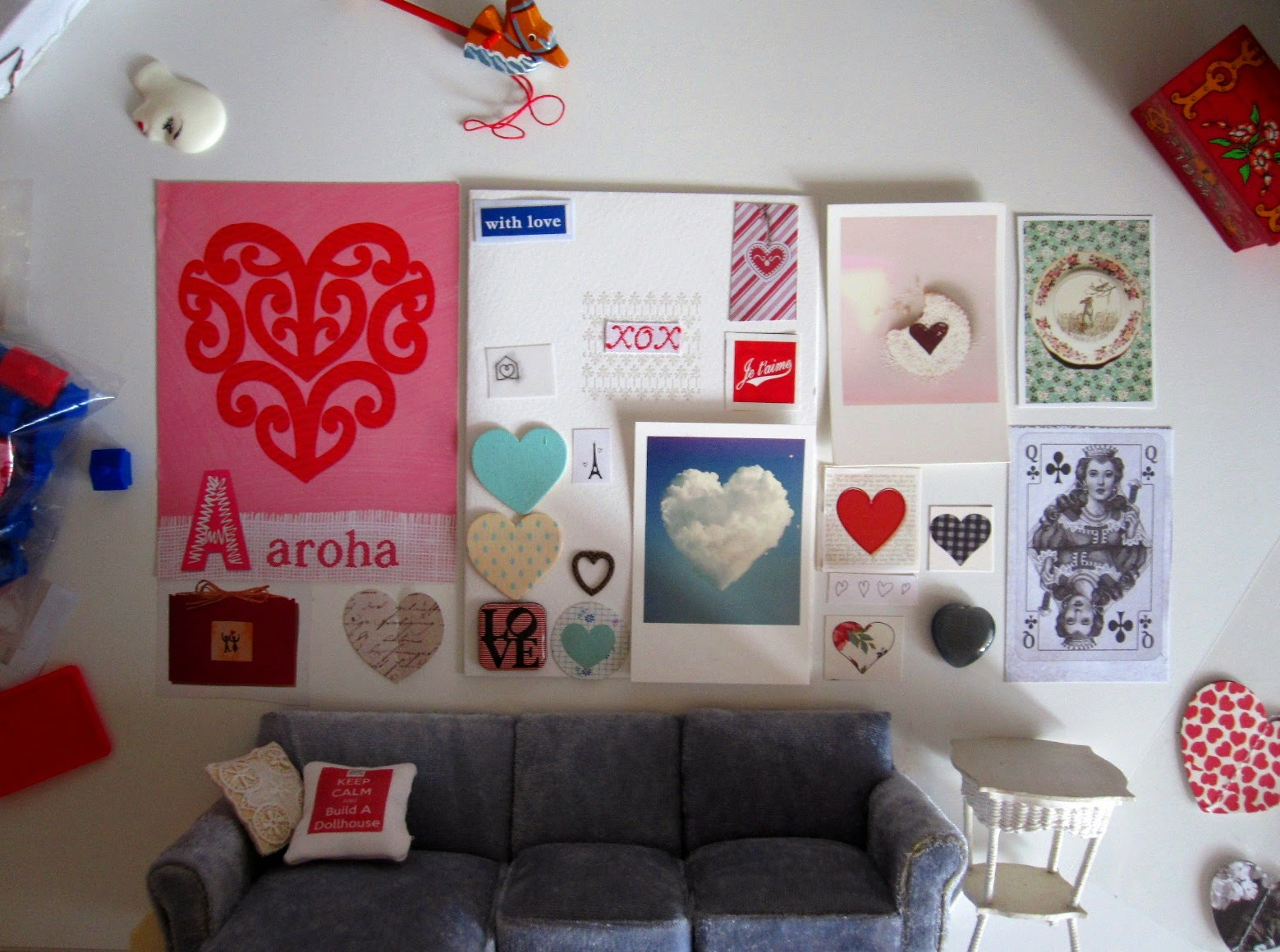 Modern dolls' house miniature grey sectional sofa and cane table with a selection of heart-themed images arranged 'above' them on a wall (actually a desk, with the dolls' house furniture tuned sideways).