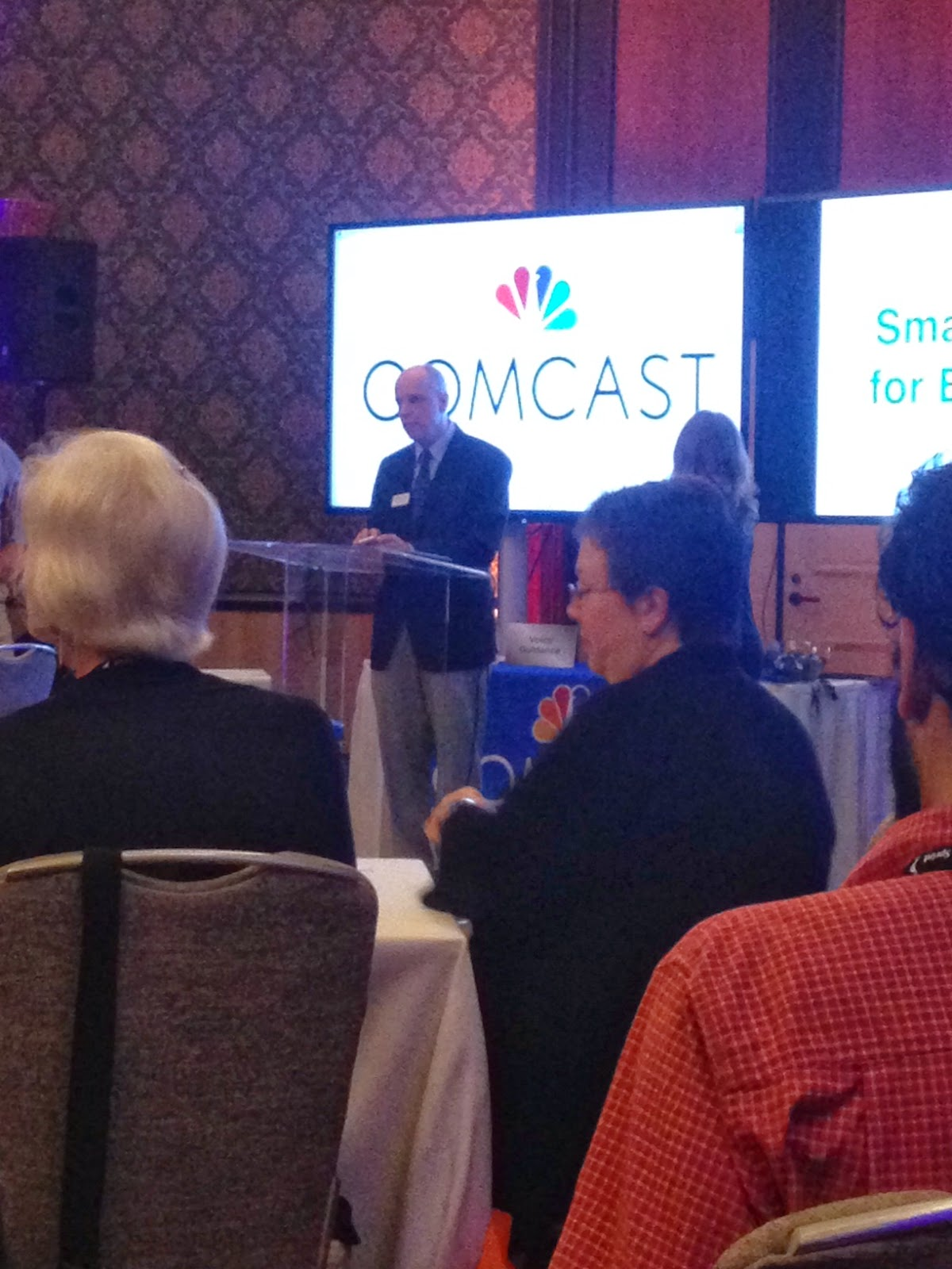Man standing in front of podium with a lare screen in the background that says comcast. Also two women sitting at  table listening to presenter