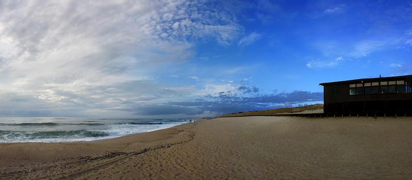 Panorama da praia deserta com o bar de praia à direita