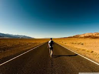 A man walking in the middle of the road towards the horizon