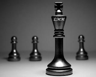 """Cette image montre quatre pieces d'un jeu d'echecs (chess). Ces pieces sont noires. Au premier plan se situe  le roi, au second plan, alignes de part et d'autre du roi se trouvent trois pions, deux a gauche et un a droite. Le fond de l'image est sombre et reste dans les tons noirs avec diverses nuances de gris, certainement dans un souci esthetique afin d'etre en adequation avec la couleur des pieces. Le roi qui apparait au premier plan porte sur le haut les lettres bien connues """"LMM"""" qui sont les initiales désignant Le Marginal Magnifique. Cette jolie image accompage le poeme jeu d'echecs du grand poete qui compare la vie a un jeu d'echecs justement. C'est l'occasion pour lui de déployer tout un arsenal de jeux de mots autour de ce theme, mais surtout de revendiquer clairement le statut de roi tout en refusant celui de pion. En somme le theme du jeu d'echecs est le pretexte pour aborder des questions plus graves comme l'ordre social, la place en societe de chacun et les problemes qui regissent cette espece de jeu. Encore un poeme fort du Marginal Magnifique !"""