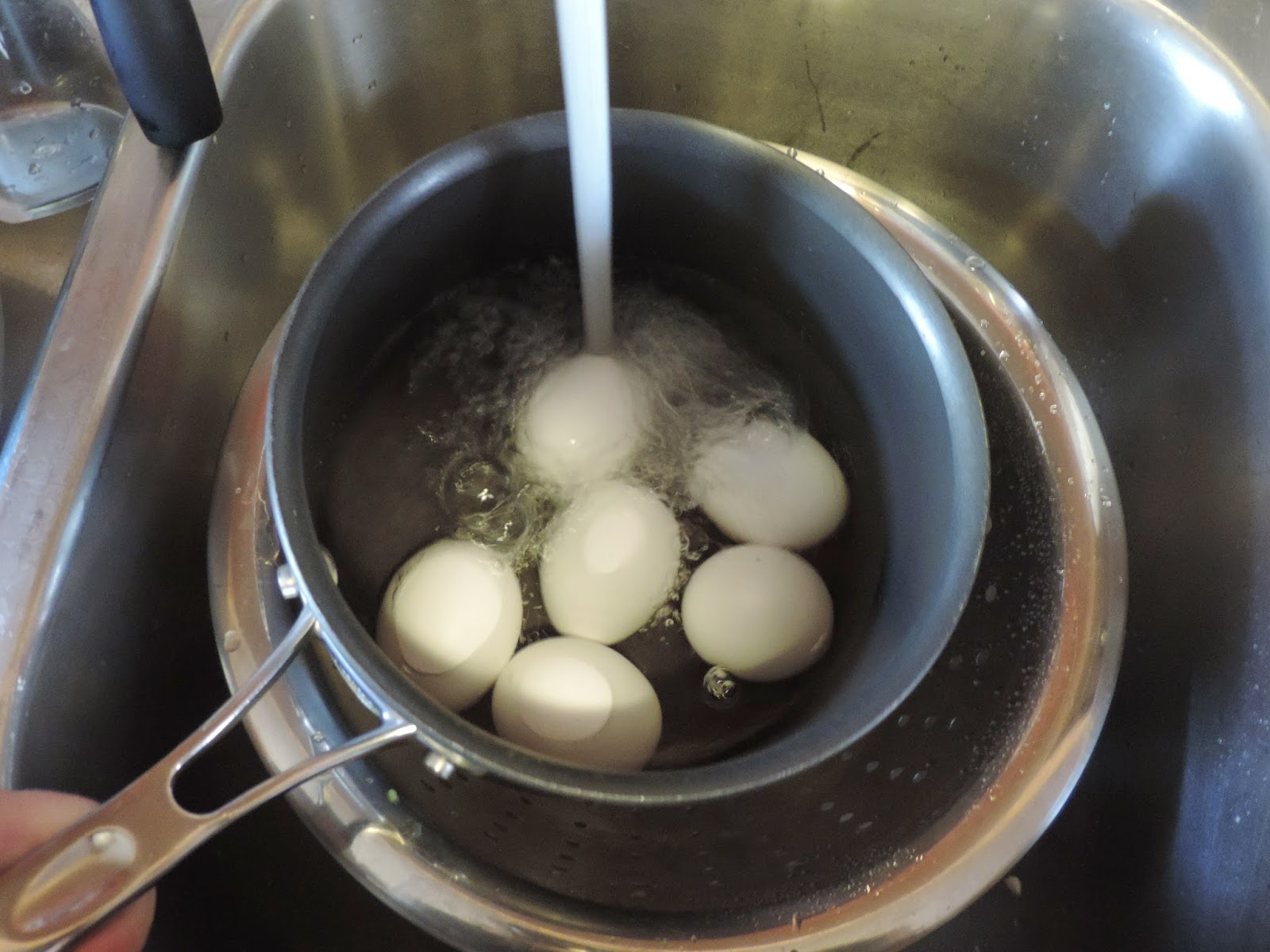 Water being added to the pot with the eggs in it.