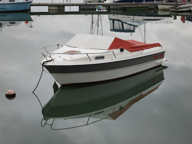 Moored boat with still-water reflection