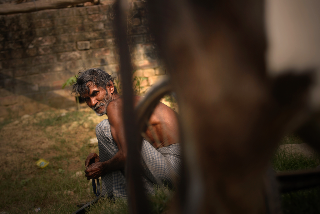 A local day worker preparing straps for a rickshaw in India