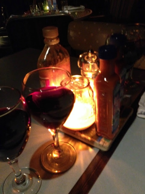 2 glasses of wine and a candle with some bottles of sauces