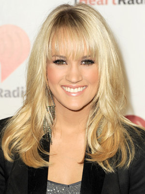 Carrie Underwood shows off her wispy bangs with a voluminous, wavy hairstyle.