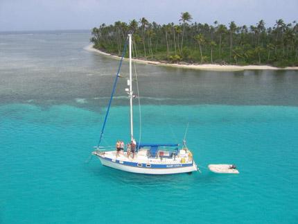 paisagem da praia com barco no mar de águas cristalinas, areia branca e vegetação