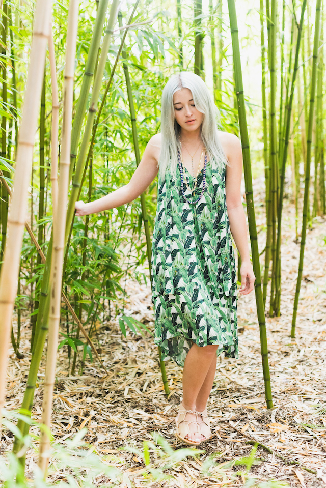 Bryn Newman of Stone Fox Style in Rebecca Minkoff Summer Travel Essentials. Wanderlust travel outfit ideas. palm tree leaf print dress and layered necklaces make for a cute and easy summer outfit.