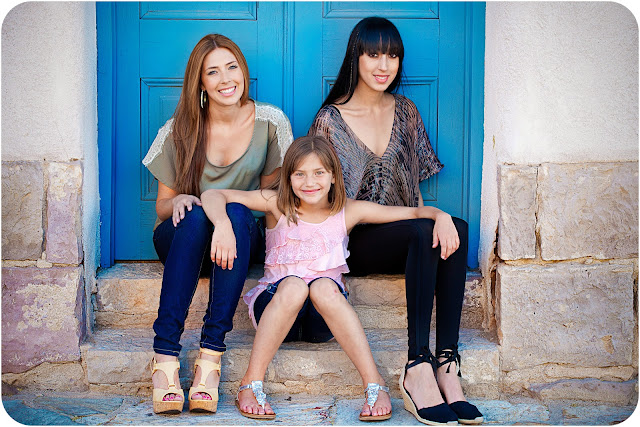 Three gorgeous sisters sitting on steps posing for a family portrait