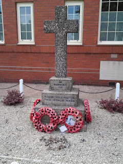 A concrete and pepple dash cross on a base of stepped blocks.  There are poppy wreaths all around the base.  The memorial stands in front of a red brick structure with narrow windows