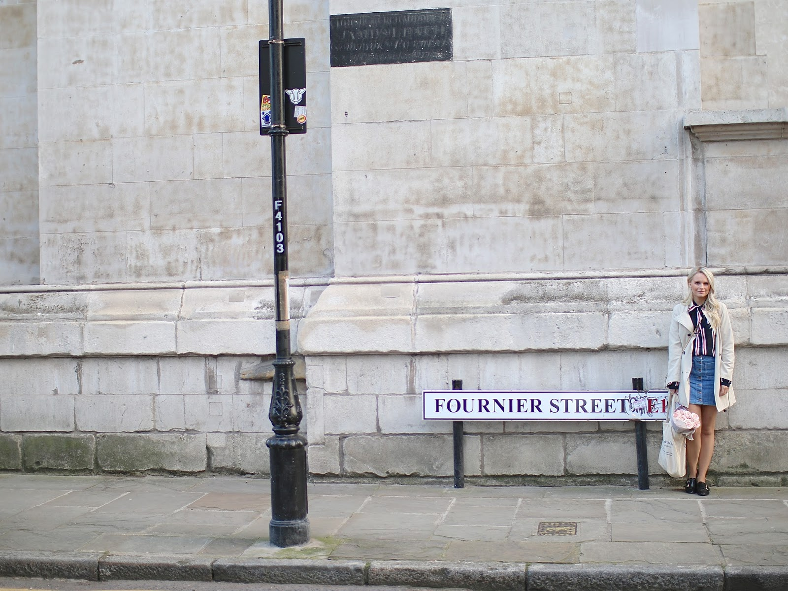 a women stands in front of pretty street sign in london, wearing a light blue denim skirt with buttons from Zara