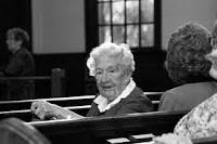 old woman sitting in a Pew