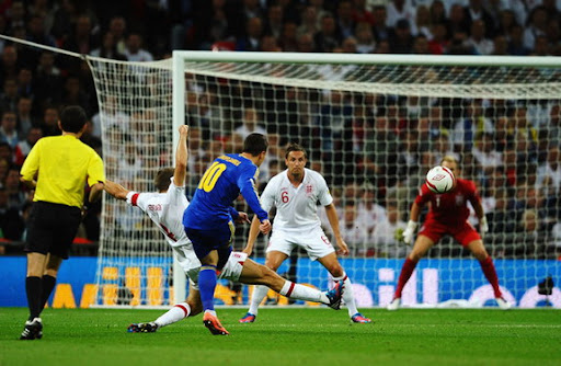 Ukraine player Yevhen Konoplianka shoots past Steven Gerrard to score against England