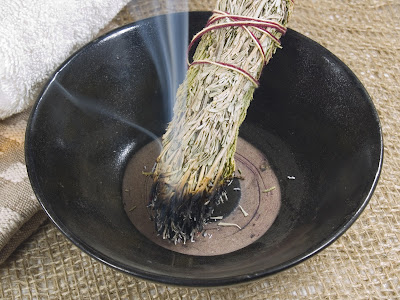 bowl with burning sage smudge stick