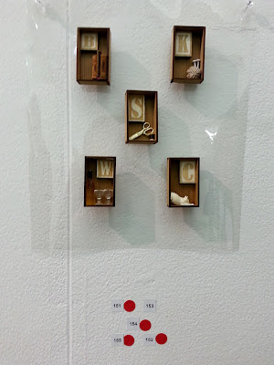 Five miniature brooches on display in a gallery, with four red dots underneath them.
