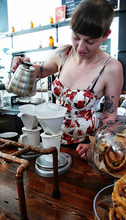 Tattooed tea maker in a flowery dress at Heritage General store.