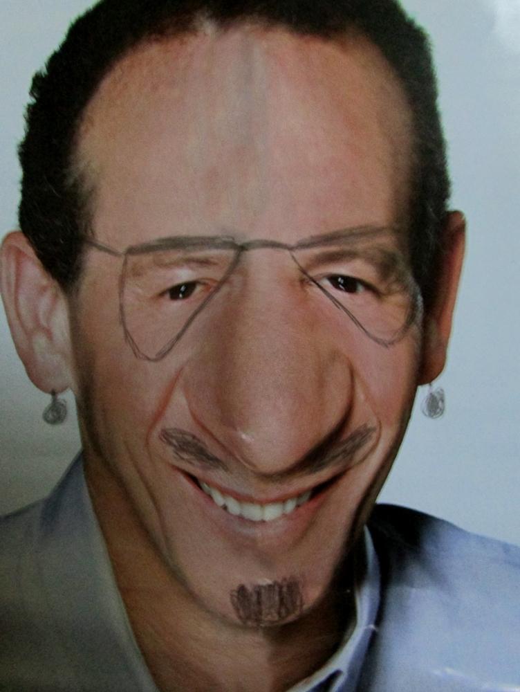 Foto do rosto de um candidato, com rabiscos simulando um óculos, barba e bigode. O queixo foi alterado, deixando-o mais baixo e fino. O nariz foi amplificado, tornando-se mais oval.