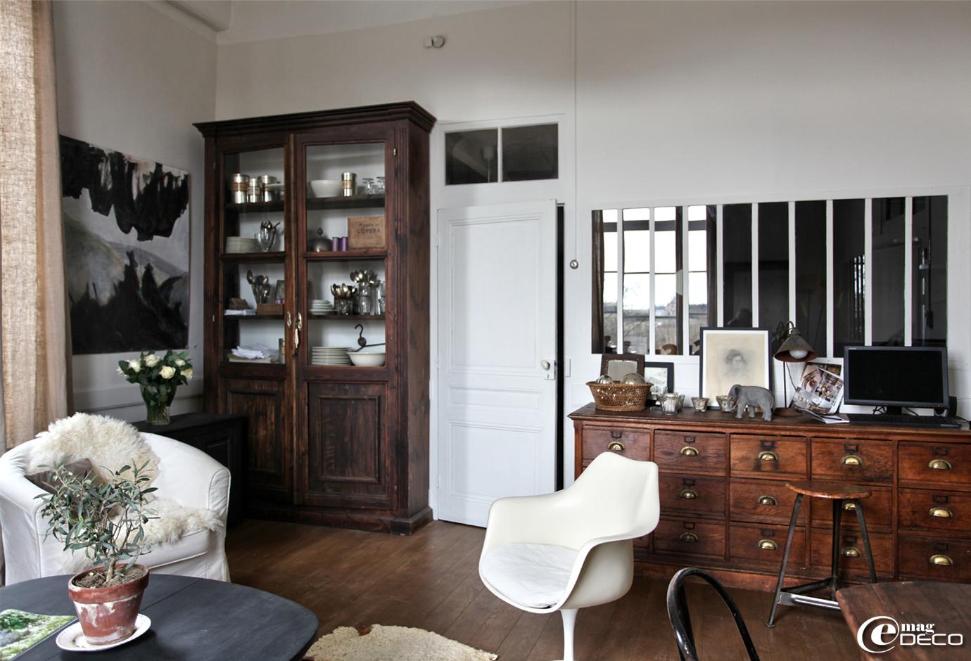 Une ancienne verrière d'atelier perce une cloison. Un meuble à tiroirs de grainetier et un tabouret industriel chinés à Avignon. Un fauteuil Tulipe d'Eero Saarinen chiné à Lyon