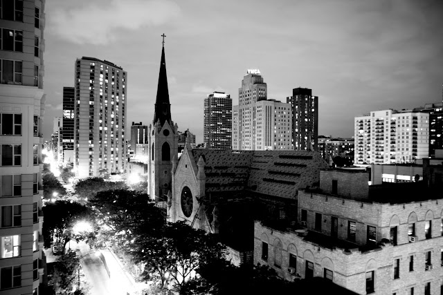 A very of buildings and a church in Chicago at night from an apartment balcony.