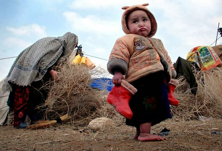 An Afghan child holds a pair of boots in a camp for the internally displaced on the outskirts of Ma