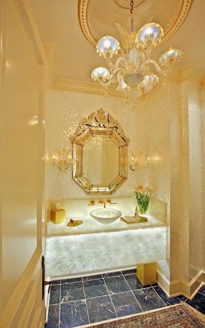 beautiful glowing powder room with stunning chandelier, floating vanity and elegant mirror by RSVP Design