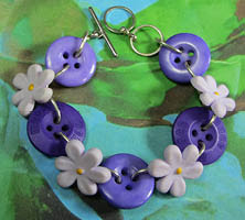 Cute purple daisy bracelet has light purple flowers and dark purple buttons linked together with silver loops