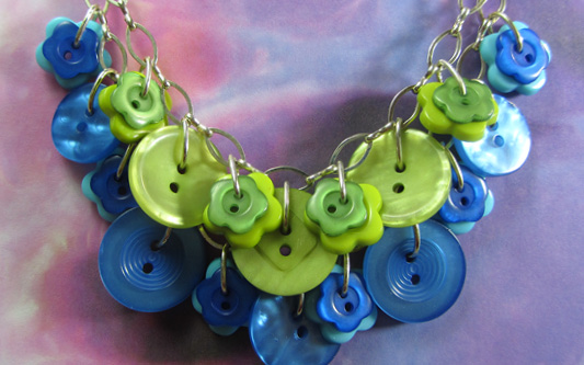Layered necklace has green and blue fashion buttons on two strands of silver chain
