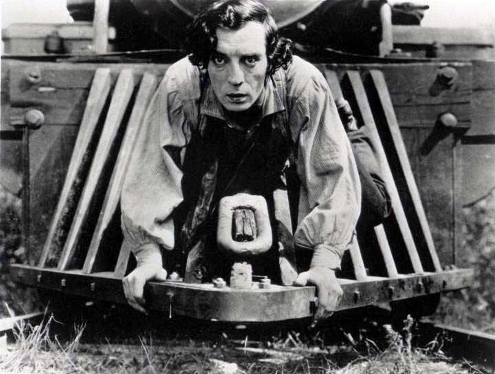 Fotograma del Maquinista de la General que muestra a Buster Keaton subido en una locomotora al borde del suelo y las vías