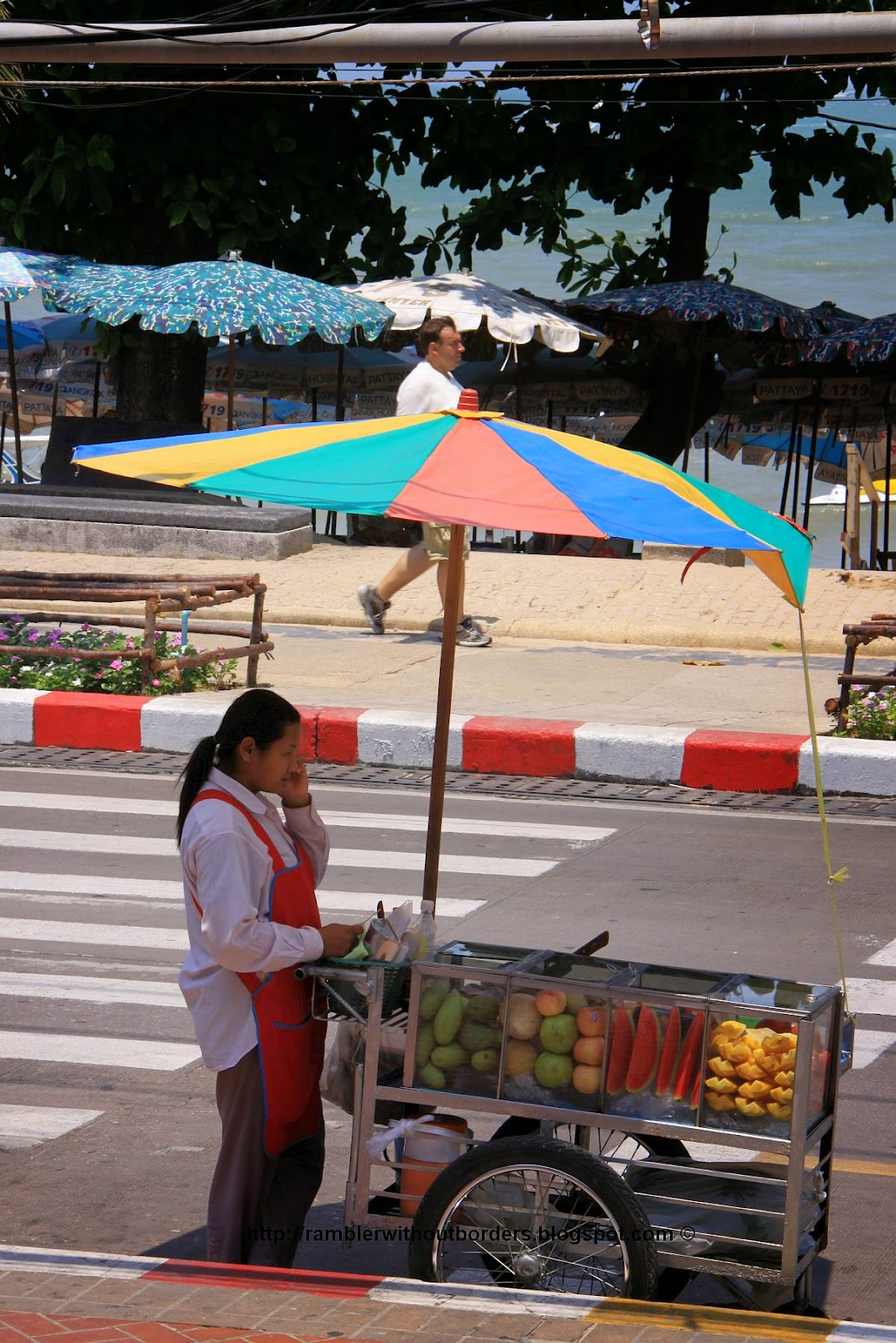 Itinerant street vendor selling fruit on a mobile phone, Pattaya, Thailand