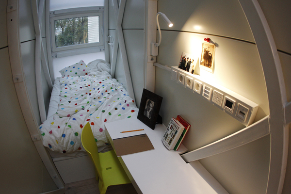 Picture of small working desk and green chair by the bed in the bedroom of the world's narrowest house
