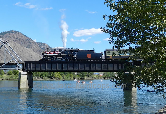 The train sits on the bridge over the river and welcomes the canoes
