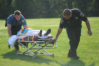 Emergency responders wheel a student participant to a waiting ambulance during a drill.