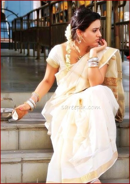 Actress Aksha breaking coconut in white traditional saree