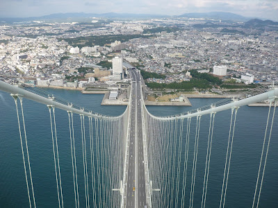View of Maiko, Kobe from the top of the main tower of the Akashi Kaikyo Bridge. The Main Suspension cables stretch down to an anchor on the Maiko side and support the road deck 300m below where there are many cars visible.