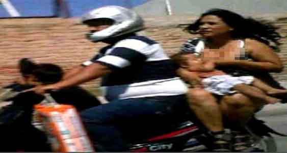 Ibu menyusui anaknya sambil naik motor