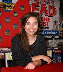 A photo of Fiona Staples, a brown-haired woman of First Nations descent, seated at a signing table.