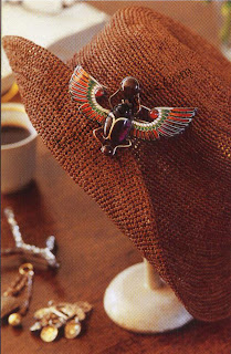 Scarab pinned to a straw hot. The color of the straw matches the colors of the enameled wings.