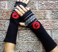 "Hands and forearms wearing ""wristers"" of black knit material, decorated with gray zig-zag pattern with red circular accent sewn on."