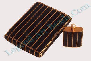 A gold cigarette case and lighter set with a freshwater pearl and enameled in opaque matt black enamel; designed and enameled by Oskar Pihl in 1934.