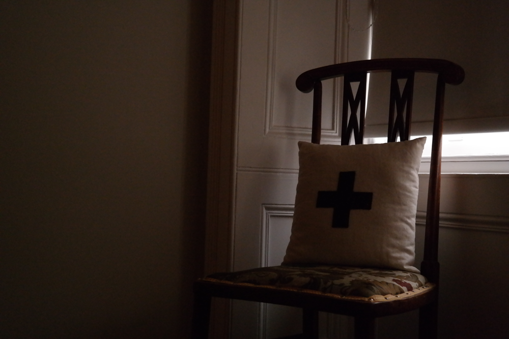 Cushion on a wooden chair in a room lit only by light around a window blind