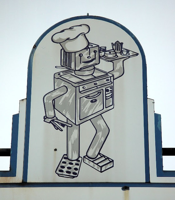 Restaurant sign of robot comprised of various kitchen appliances.