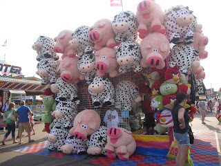 Bulbous pink pigs and black and white spotted cow stuffed animals hanging all over a booth