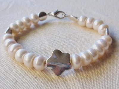 pulsera artesanal de perlas de rio con adorno de flor en el centro y cierre mosqueton