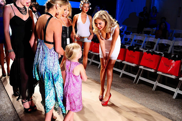 Kate Upton  talking with a child in Show