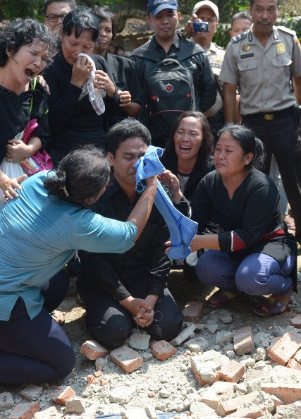 Indonesian Christians crying and praying Indonesian Christians