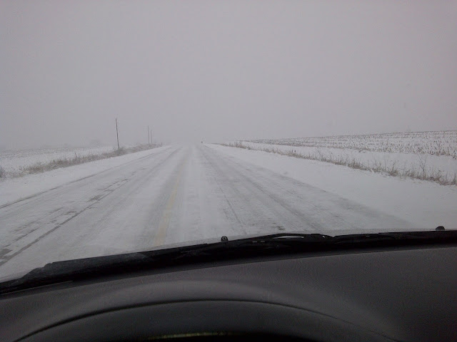 View out windshield of 100% snow covered road on rural highway