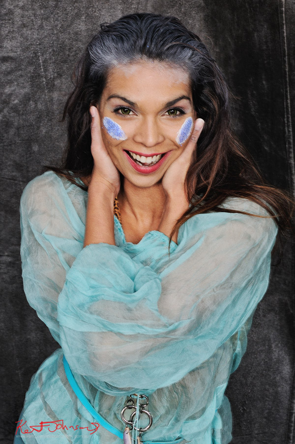 Sage Godrei, magazine style actors portrait; studio photography, Headshot laughing, Sage in fantasy outfit, mid shot.