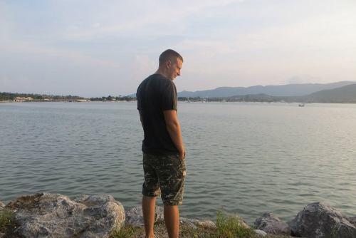 Стройный парень стоит у моря