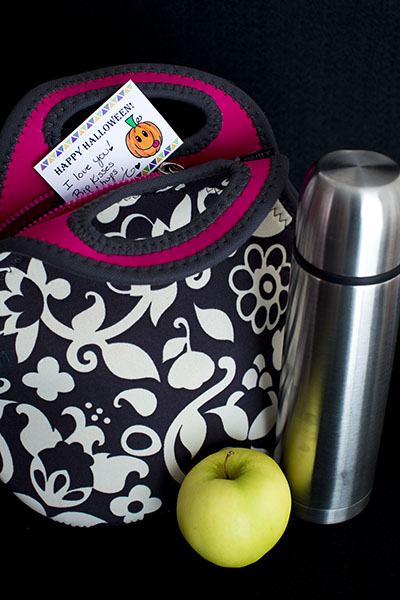 Halloween lunchbox note tucked into the top of a black and white paisley lunchbox next to a silver thermos and a bright green apple all on a dark black background.