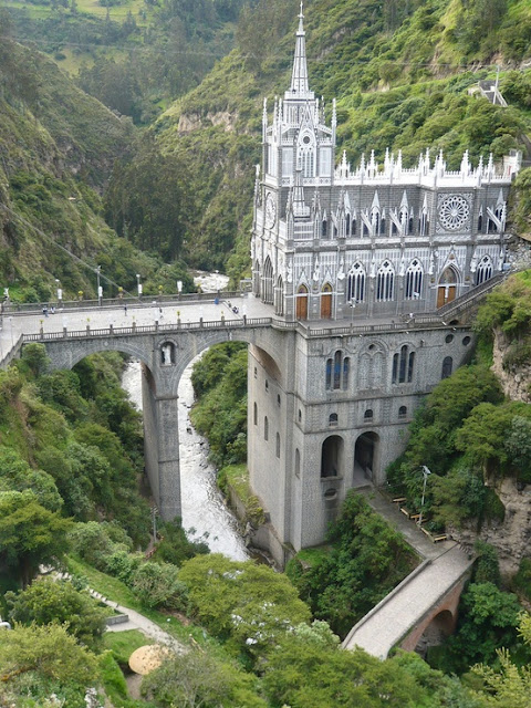 """Las Lajas Sanctuary (Spanish: Santuario de Las Lajas) is a minor basilica church located in the southern Colombian Department of Nariño, municipality of Ipiales and built inside the canyon of the Guáitara River. The present church was built in Gothic Revival style in 1949. The name Laja comes from the name of a type of flat sedimentary rock similar to shale.   The inspiration for the church's creation was a miraculous event in 1754 when Amerindian Maria Mueces and her deaf-mute daughter Rosa were caught in a very strong storm. The two sought refuge between the gigantic Lajas, when to Mueces's surprise, her daughter Rosa exclaimed """"the mestiza is calling me"""" and pointed to the lightning-illuminated silhouette over the laja. This apparition of the Virgin Mary instigated popular pilgrimage to the site and occasional reports of cases of miraculous healing. The image on the stone is still visible today.  The existence of a shrine in this location was recorded in the accounts of friar Juan de Santa Gertrudis's journey through the southern region of the New Kingdom of Granada between 1756 and 1764. The first shrine was built here in the middle of 18th century from straw and wood. It was replaced with a new, larger shrine in 1802, which in turn was extended and connected to the opposite side of canyon with a bridge.  The current church was built between January 1, 1916 and August 20, 1949, with donations from local churchgoers. It rises 100 m high from the bottom of the canyon and is connected with a 50 m tall bridge to the opposite side of the canyon."""